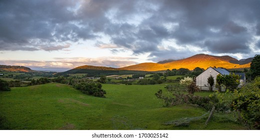 A landscape of a rural area on the Mourne Mountains under a cloudy sky in Northern Ireland