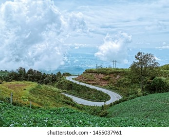 Landscape of S curved road up in the mountain surrounded by green agriculture and cabbage garden on the slope
