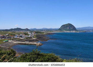 Landscape of Sagye-ri village and southwestern coast of Jeju Island with Sanbangsan and Hallasan mountain, viewed from Olle trail No.10 at Songaksan mountain.