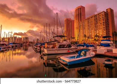 Landscape of sailing boats and yachts docked at the Ala Wai Harbor, the largest yacht harbor of Hawaii, reflecting in the sea at sunset.On background, a luxurious hotel near Waikiki beach in Honolulu.