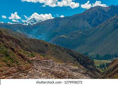 Landscape of the salt terraces and ponds of Maras with the snowcapped Andes peak of the Salkantay in the region of Cusco, Peru.
