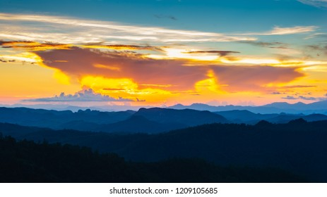 Landscape scene of colorfull sunset sky with mountain range and forest.