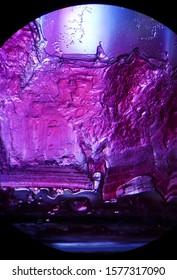 Landscape scene hidden in a microscopic salt crystal precipitated on the glass wall
