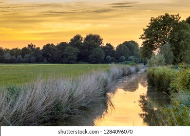 Landscape scene over river and road at sunset in flat agricultural area in Groningen province the Netherlands