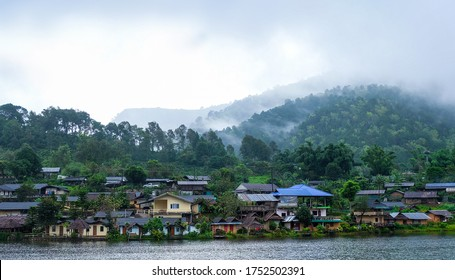The landscape scene of a small urban Chinese village on the green hill with fade mist beside the reservoir name's Baan Rak Thai, the famous vacation traveler landmarks in Mae Hong Son, Thailand.