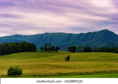 Landscape scenic view of Cades Cove Valley under cloudy skies in Tennessee's Great Smoky Mountians