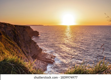 Landscape of sea with montains, dramatic wave and rock in sunset.