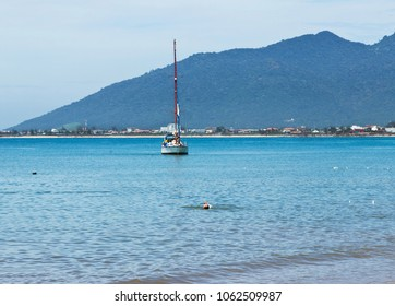 Landscape of the sea with sailboat and man swimming