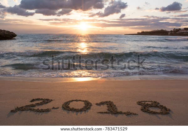 Landscape With Sea At Sunrise And The Sign 2018 Written On The Sand On Cloudy Sky Background