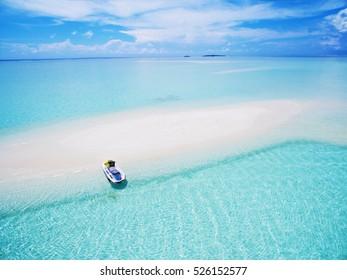 Landscape seascape aerial view over  Maldives Male Atoll sandbank island. Jet ski at the white sandy beach