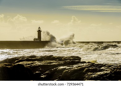 Landscape seascape lighthouse battered by huge waves on Atlantic Ocean with blue green skies and puffy clouds.