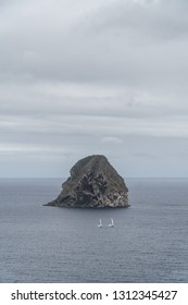 Landscape seascape view of the famous Diamond rock (rocher du Diamant) in the sea with grey sky, clouds & two sailing boats floating together with their white sail, Martinique, Antilles, West Indies.