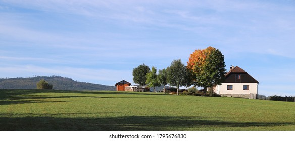 landscape with secluded homestead in the autumn with colored tree leafs
