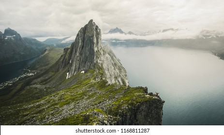 Landscape Segla Mountain over clouds and fjord in Norway. Travel location scenic Senja islands. Dreamy landscape, misty sunrise in a beautiful valley below