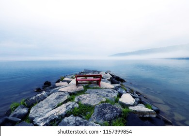 Landscape with Seneca lake under the fog, Finger lakes, New York state, raining day scenery, foggy lake background, stony bank with red bench.