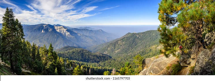 Landscape in Sequoia National Park in Sierra Nevada mountains on a sunny day; smoke from wildfires visible in the background, covering the Fresno area;