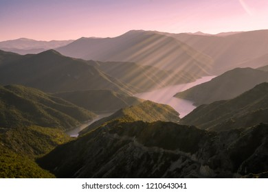 Landscape shot of a lake surrounded by mountains, sun rays falling down in the centre of the photo, pink hue