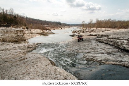 Landscape shot at the river bed with water flowing down the center of a rocky crevasse and a off road vehicle driving along the rock heading towards the camera.