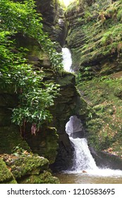 Landscape shot of a waterfall with water cascading down a mossy rockface and flowing through a hole