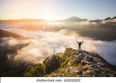 Landscape with silhouette of a standing happy man with backpack and raised-up arms on the mountain peak on the background of cloudy sky at colorful sunset in summer.