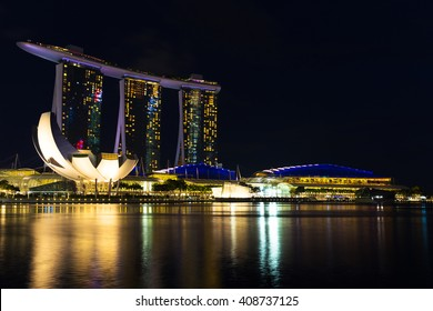 Landscape of the Singapore Marina Bay hotel, bridge, museum and financial district at night