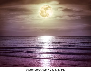 Landscape of sky with dark cloudy and bright full moon over seascape in the evening.