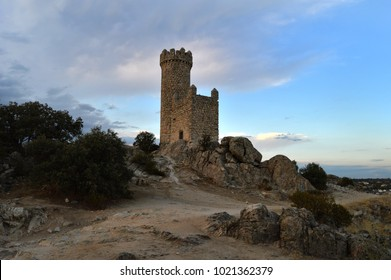 Landscape with a small hill and the watchtower of the tower of the Lodones in summer at sunset. In Torrelodones province of Madrid. Spain