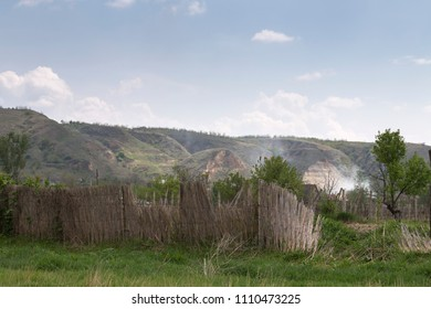 Landscape with smoke. The reed fence is located in the foreground and picturesque hills are located in the background.
