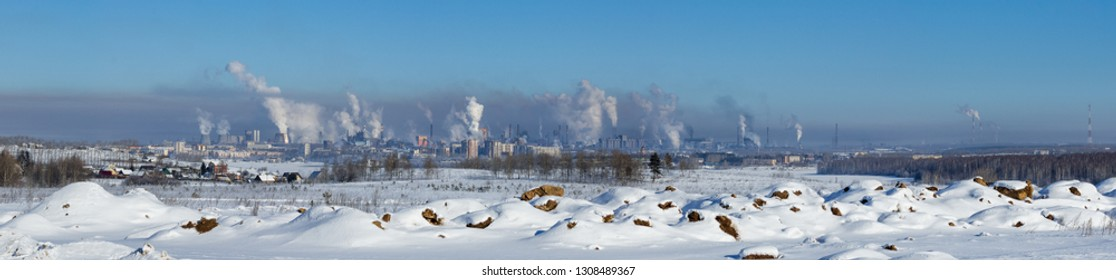 Landscape of smoking chimneys of factories in an industrial city. Dangerous ecology in the industrial city. Smoke and smog from factories and plants.