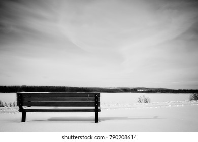 landscape with snow and alone empty bench