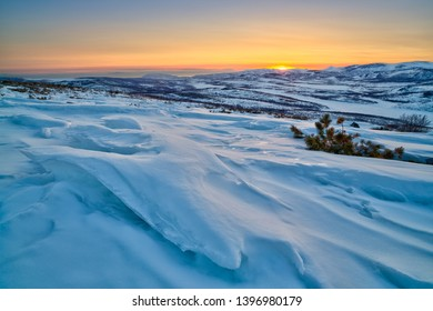 Landscape with snow drifts on the hillside. Sastrugi (zastrugi) formed on the surface of snow by wind erosion. View of the valley among the mountains. Beautiful northern sunset. Magadan Region, Russia