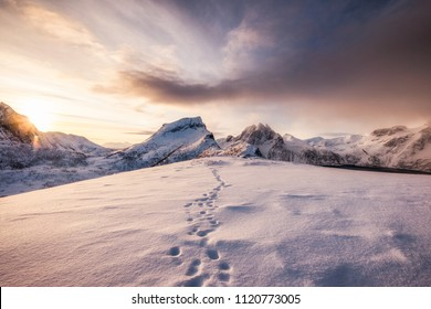 Landscape of snow mountains range with footprint on snowy at sunrise morning