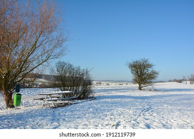 Landscape in the snow, with table and benches, with blue sky in Germany, Bavaria, Spessart