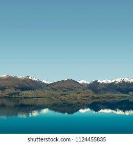 Landscape of snowy mountain peaks with blue and clear sky in front of a huge calm lake. The mountains are reflected on the water like a mirror.