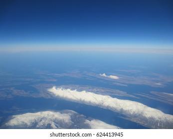 Landscape of snowy mountain range, ocean, blue sky, and islands