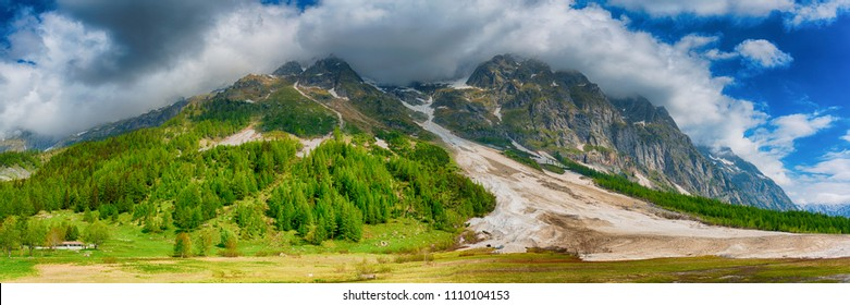 Landscape in spring season in the Ferret valley with avalanche in foreground and clouds and blue sky in background, Courmayeur - Italy