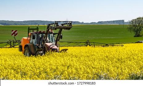 Landscape in spring - A tractor on a bright yellow flowering rape field, spraying a chemical solution on the field, on a sunny day at Marburg in Germany.
