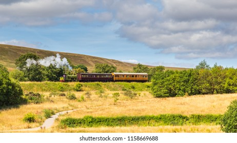 Landscape with steam train of the heritage railway  in Blaenavon driving along Garn Lakes Local Reservce in Wales, UK