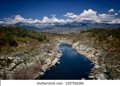 Landscape of stony mountain river with forests and clouds