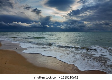 Landscape with stormy sky over the winter sea and sandy beach