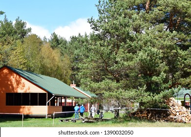 Landscape with summerhouse building, pine trees and senior people walking on yard.