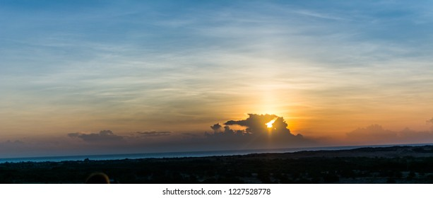 Landscape of sun over skyline in desert at White Sand Dunes Mui Ne, Vietnam. Countryside panorama under scenic colorful sky at sunset dawn sunrise. Beautiful view of bright dramatic sky & dark ground