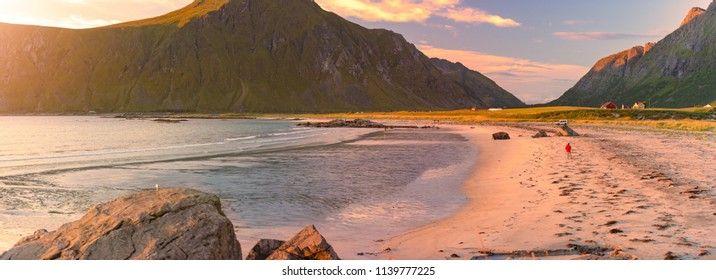 Landscape at sunset with beach and mountains. Purple sky in background. Travel in Norway, Scandinavia, Europe.