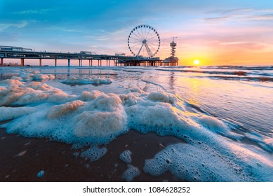 Landscape of a sunset at the beach and the pier of Scheveningen with nobody, no tourists, The Hague, Netherlands