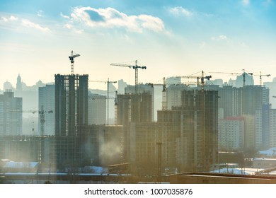 Landscape sunset in the city with buildings, blue sky, sun and industrial cranes
