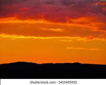 Landscape with sunset and silhouettes of trees. Beautiful view of bright colorful sky happened on evening decline in the summer evening.