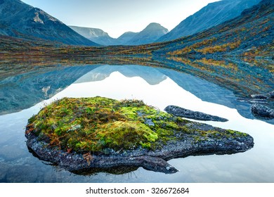 Landscape of Tahtarjavr lake with transparent water, rocky bottom and large fish-like rock on the foreground, and distant mountains on the background, Hibiny mountains above the Arctic circle, Russia