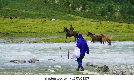 Landscape, there are tourists, a horseman stands against the mountains, horses and a river flows, a picturesque place illustrating the rest