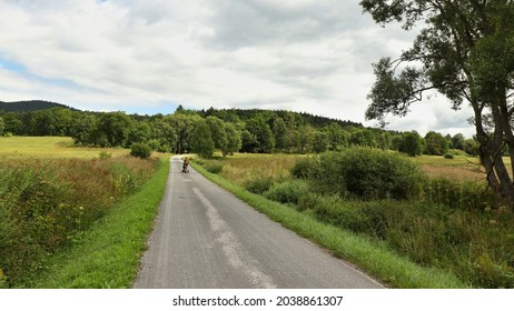 A landscape with a tourist on the road. Location: Europe, Czechia, near Horni plana
