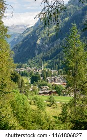 landscape with touristic mountain village among green woods, shot on a bright summer day at Gressoney Saint Jean,  Lys valley, Aosta, Italy